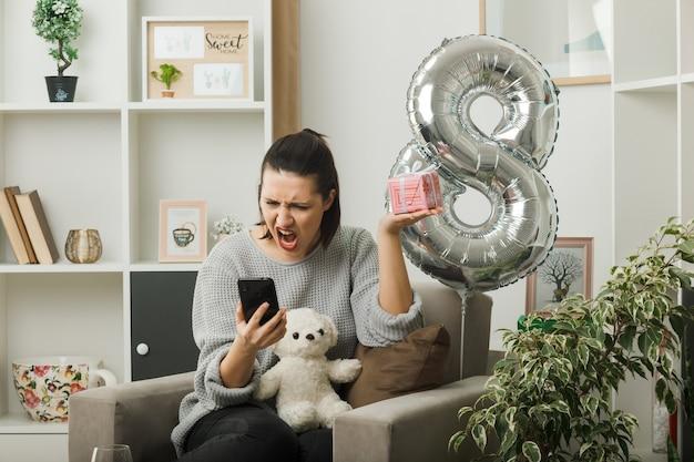 Сердитая красивая девушка в счастливый женский день держит подарок, глядя на телефон в руке, сидя на кресле в гостиной