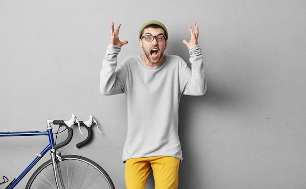 怒りのバイクインストラクターが怒りの表情と手を挙げて叫び、何もわからない生徒たちに怒っています。グレーに分離された真剣な表情で叫んで若いサイクリスト