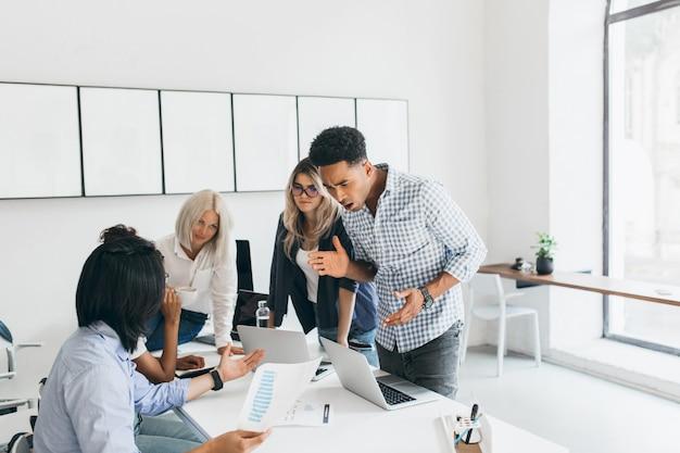 テーブルの近くに立って手を振っている怒っている黒い首長。ノートパソコンの画面を見て、青いシャツを着たアジアのプログラマーに何かを話している不幸なマネージャーの屋内の肖像画。