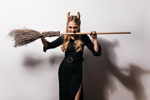 흰 벽에 서있는 성 난 금발 마녀. 할로윈에 빗자루와 함께 포즈를 취하는 뱀파이어 소녀.