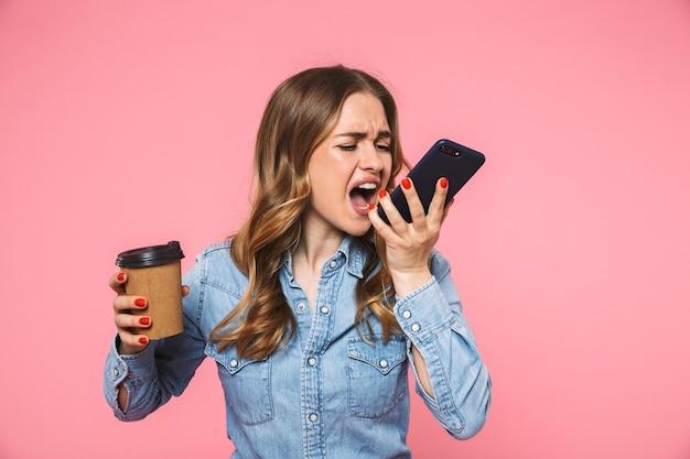 一杯のコーヒーを保持し、ピンクの壁を越えてスマートフォンで叫んでデニムシャツを着て怒っている金髪の女性