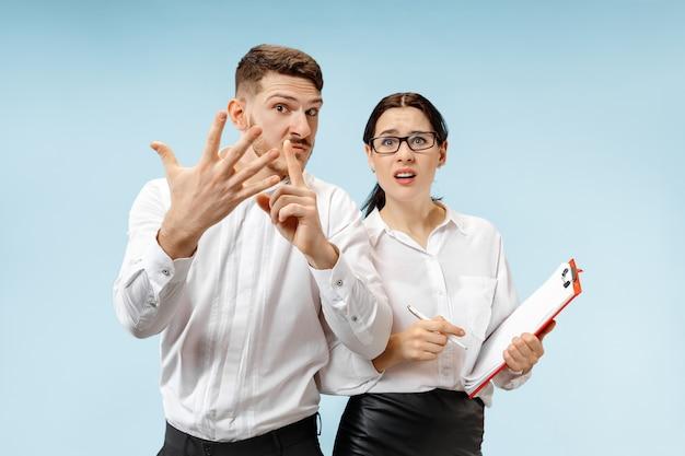 怒っている上司。男と彼の秘書はオフィスに立っています。彼の同僚に叫んでいるビジネスマン。女性と男性の白人モデル。オフィス関係の概念、人間の感情