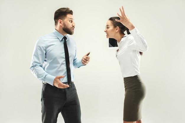 Злой босс. человек и его секретарь, стоя в офисе или студии. деловой человек, указывая на камеру со своим коллегой. женские и мужские кавказские модели. концепция офисных отношений, человеческие эмоции Premium Фотографии