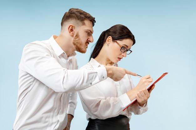 怒っている上司。男と彼の秘書はオフィスやスタジオに立っています。彼の同僚に叫んでいるビジネスマン。女性と男性の白人モデル。オフィス関係の概念、人間の感情