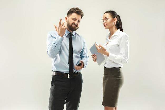 Злой босс. человек и его секретарь, стоя в офисе или студии.