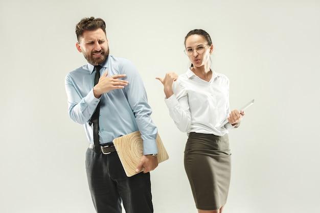 怒ったボス。男と彼の秘書がオフィスまたはスタジオに立っています。