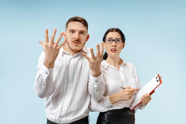怒っている上司。男と彼の秘書はオフィスやスタジオに立っています。