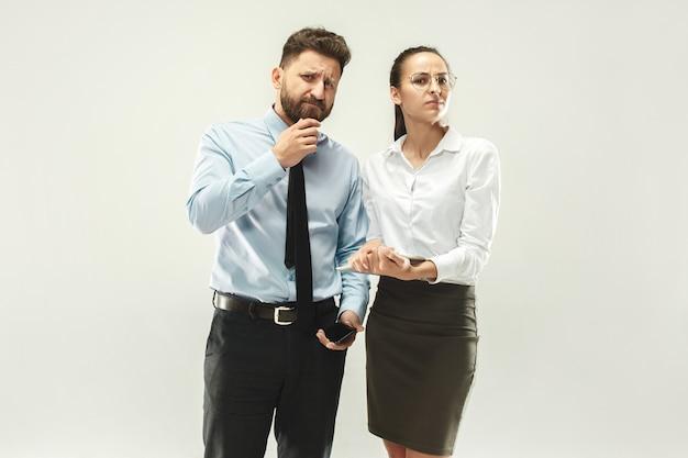 怒ったボス。男と彼の秘書が事務所に立っています。