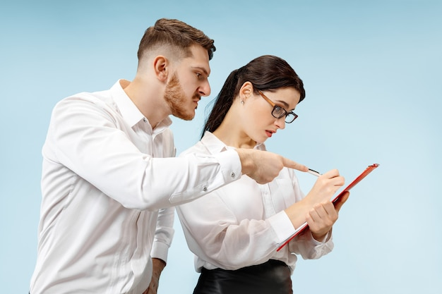 Angry boss. man and his secretary standing at office or studio. business man screaming to his colleague. female and male caucasian models. office relationships concept, human emotions