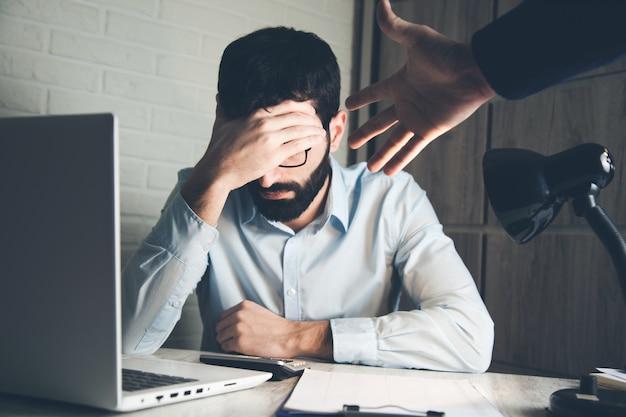 Злой босс с грустным человеком на офисном столе