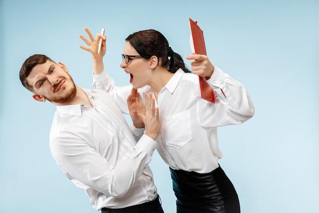 怒っている上司。女性と彼の秘書がオフィスに立っています。彼の同僚に叫んでいる実業家。女性と男性の白人モデル。オフィス関係の概念、人間の感情