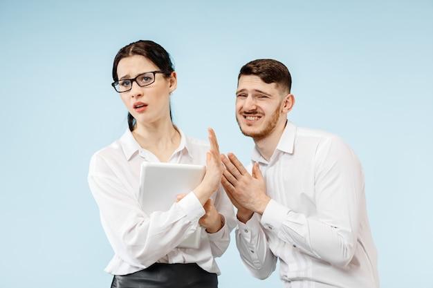 怒っている上司。オフィスやスタジオに立っている女性と彼の秘書。彼の同僚に叫んでいるビジネスマン。女性と男性の白人モデル。オフィス関係の概念、人間の感情