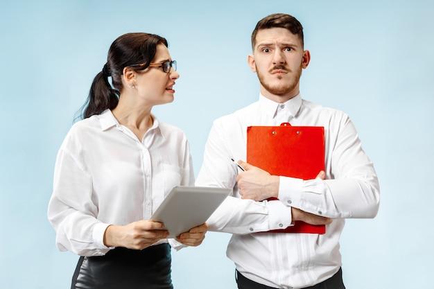 怒っている上司。オフィスやスタジオに立っている女性と彼の秘書。彼の同僚に叫んでいる実業家。女性と男性の白人モデル。オフィス関係の概念、人間の感情