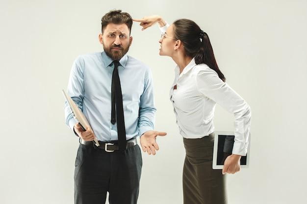 화난 보스. 사무실이나 스튜디오에 서있는 여자와 비서