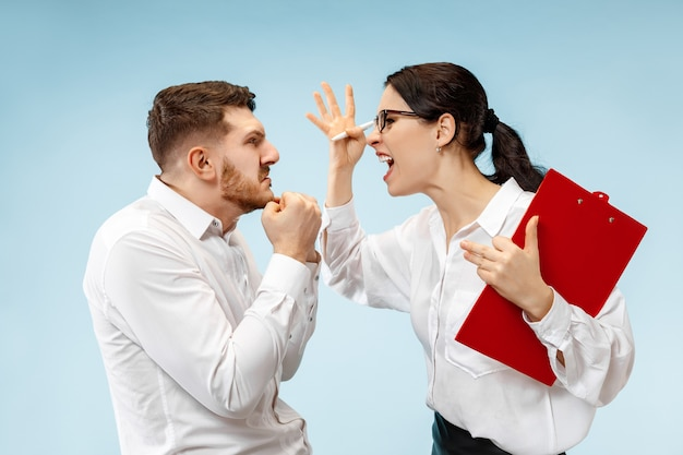 Angry boss. woman and his secretary standing at office. businesswoman screaming to his colleague. female and male caucasian models. office relationships concept, human emotions