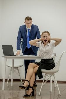 Злой босс кричит на свою молодую сотрудницу, она нервничает и расстроена