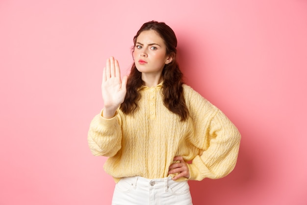Angry and bossy young woman frowning, looking serious, showing block stop gesture, stretch out hand to say no, refuse something bad, forbid action, standing against pink wall