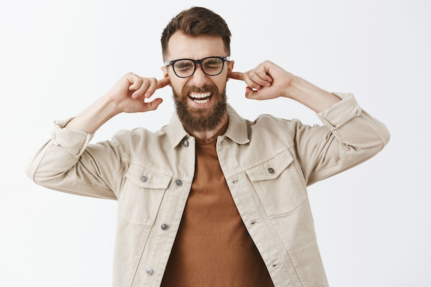 Angry bothered bearded man in glasses posing against the white wall