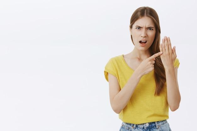 Злая обеспокоенная молодая девушка, указывая на палец без кольца