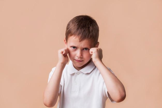 怒っている少年は戦いのために彼の拳をクリンチ Premium写真