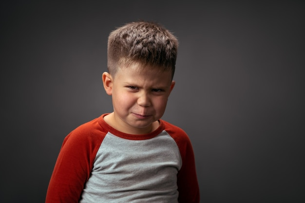 Angry boy frowning, showing with his face dislike isolated on grey background. fake child emotions