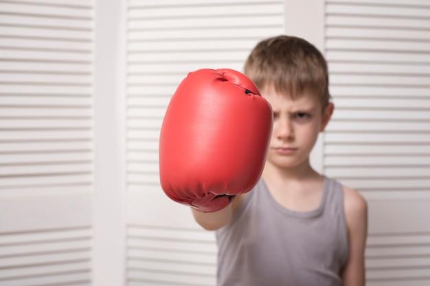 赤いボクシンググローブで怒っている少年。ヒット