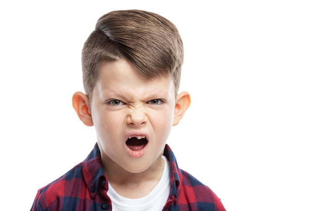 앞니가없는 7 년의 화난 소년. 확대. 흰 벽에 고립.