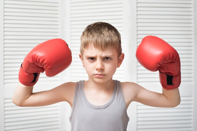 Angry boy in red boxing gloves.