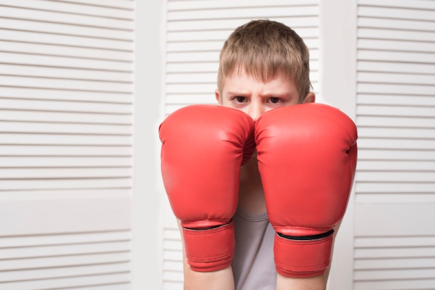 Angry boy in red boxing gloves