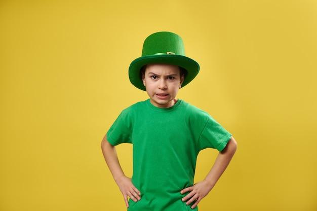 レプラコーンの緑の帽子をかぶった怒っている少年が黄色い表面でカメラにポーズ