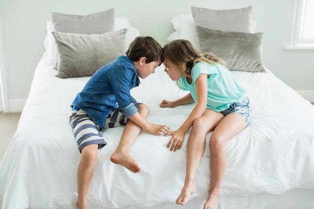 怒っている兄と妹が寝室のベッドで向かい合って