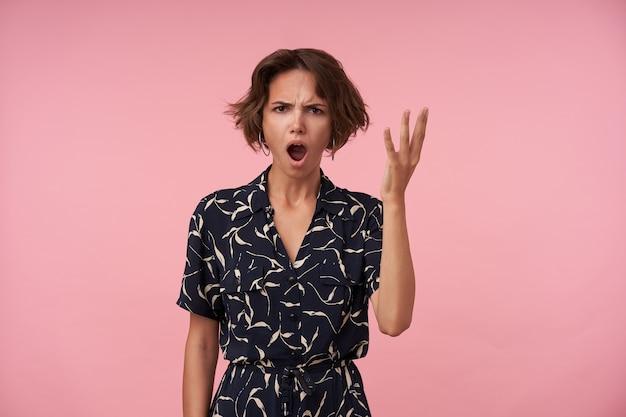 Femmina bruna arrabbiata con acconciatura casual guardando con ampia bocca aperta e viso accigliato, in posa con la mano alzata