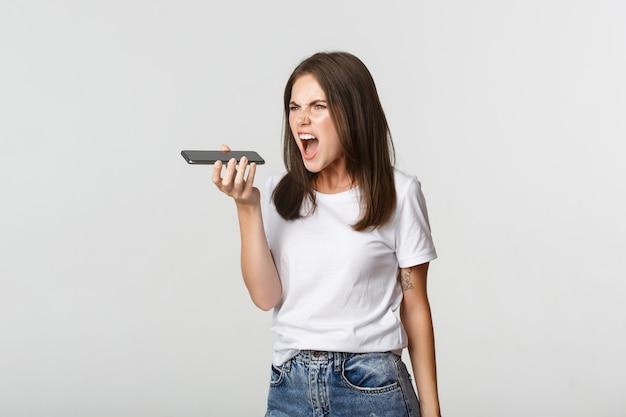 음성 메시지를 녹음하는 동안 화가 외치는 화가 갈색 머리 소녀, 분노, 흰색.