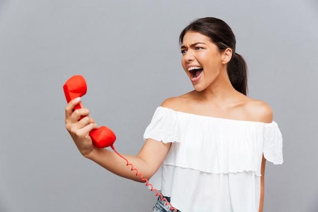 Злая брюнетка женщина кричит на телефонной трубке, изолированной на серой стене
