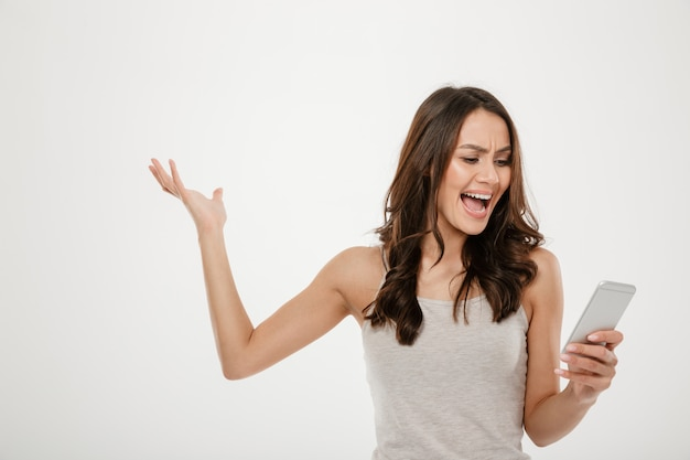 Angry brunette woman using smartphone and screaming over gray
