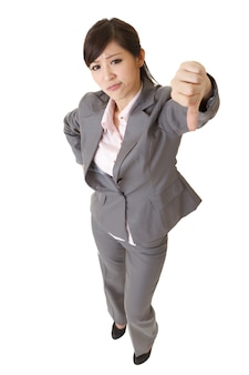 怒っているビジネスレディはあなたに親指を下に向けるジェスチャーを与えます