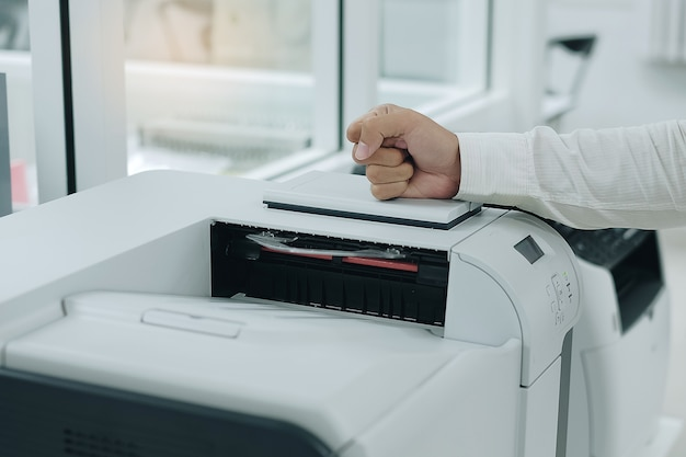 怒っているビジネスマンは、オフィスでプリンタスキャナやレーザーコピー機で彼の拳を打つ