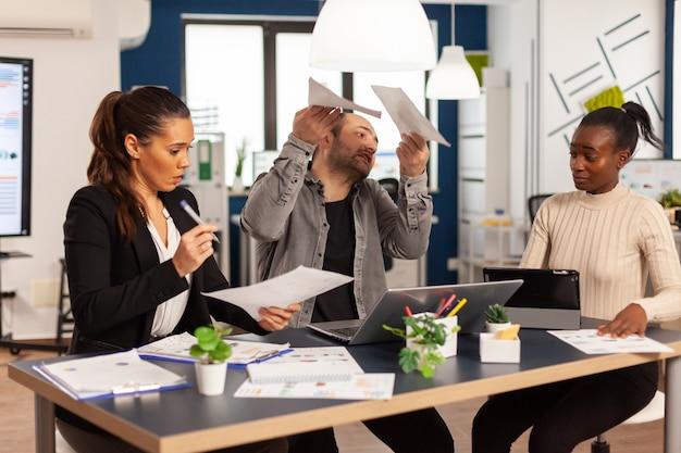 Злой деловой человек кричит на разных коллег во время офисной встречи, выбрасывая документы, не соглашаясь с плохим деловым контрактом