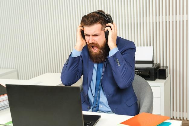 オンラインオフィスで働く怒っているビジネスマン。スーツの叫びでひげを生やした猛烈なビジネスマン。