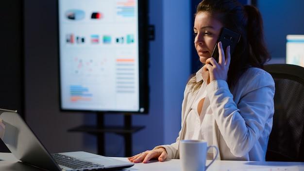 마감 시간을 준수하기 위해 금융 프로젝트에서 초과 근무를 하는 늦은 밤 창업 사무실에서 전화를 받는 화난 비즈니스 여성. 직원에게 고함을 지르는 노트북에 타이핑하는 긴장된 관리자