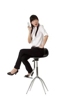 핸드폰을 들고 흰 벽에 고립의 자에 siting 화가 비즈니스 여자.