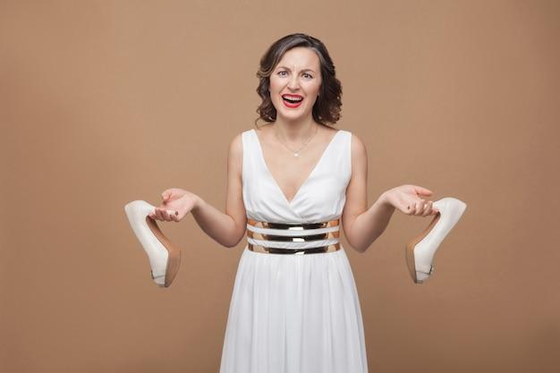 カメラの叫び声を見て、不快なハイヒールを持って立っている白いドレスを着た怒っているビジネスウーマン。感情と感情の概念。スタジオショット、屋内、薄茶色の背景に分離