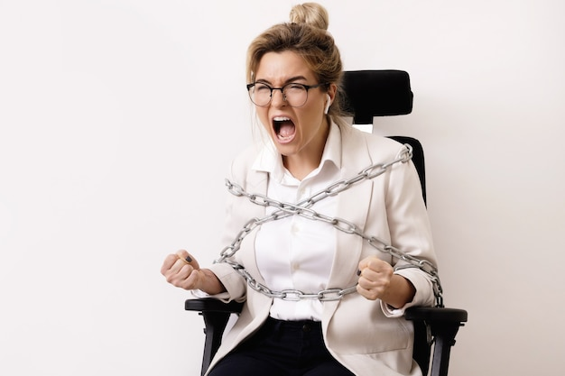 Angry business woman tied up to the office chair with a chains. concept of debts or overtime work.
