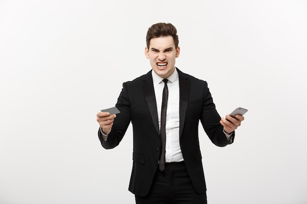 クレジットカードと携帯電話を持っている怒っている実業家。オンラインショッピングやビジネス上の問題で怒ってください。
