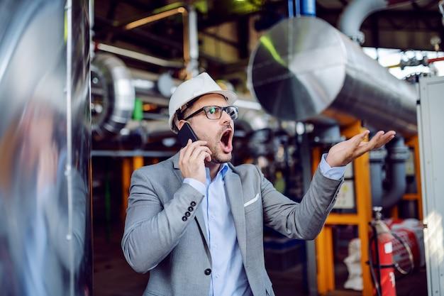 Сердитый бизнесмен в костюме и с защитным шлемом на голове крича над умным телефоном пока стоящ в электростанции.