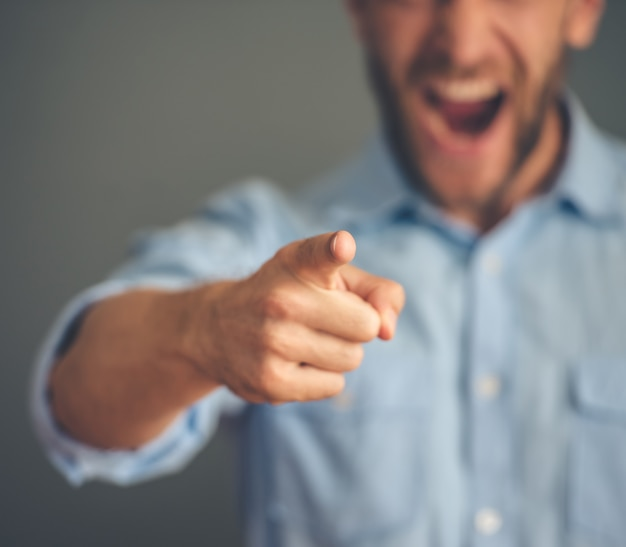 Angry businessman pointing and screaming at camera