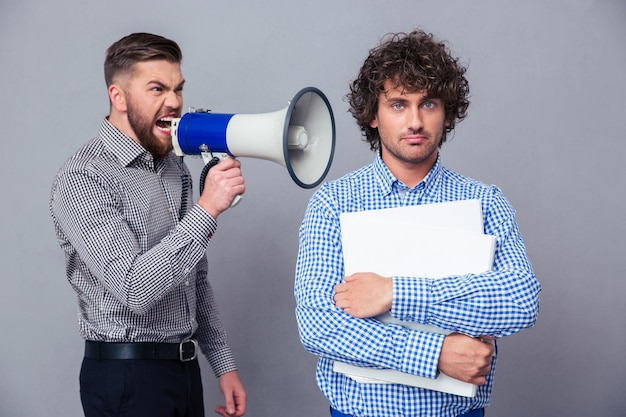 Angry businessman screaming via megaphone to another man over gray wall