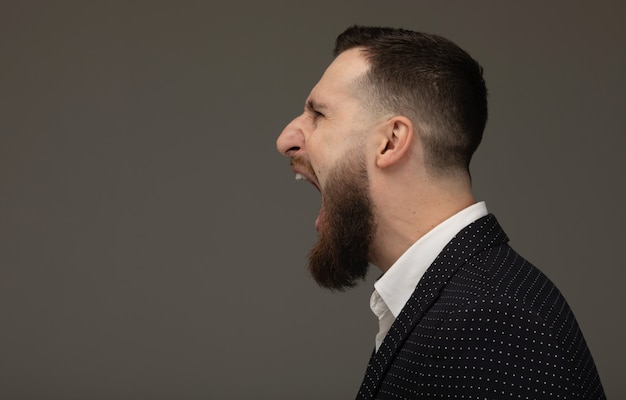 Angry businessman shouting. bearded man screaming on grey wall.