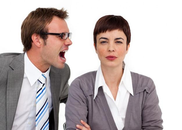 彼の同僚の耳に叫ぶ怒っているビジネスマン