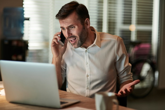 Злой бизнесмен разговаривает по мобильному телефону